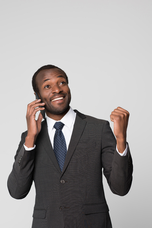 Half-length shot of cheering businessman in a suit talking on the phone and throwing his fist up.