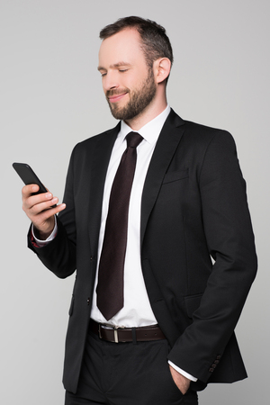 Half-length shot of young businessman in a suit looking at the screen of his smartphone and smiling. 스톡 콘텐츠