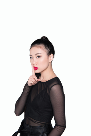 beautiful asian woman showing silence gesture isolated on white