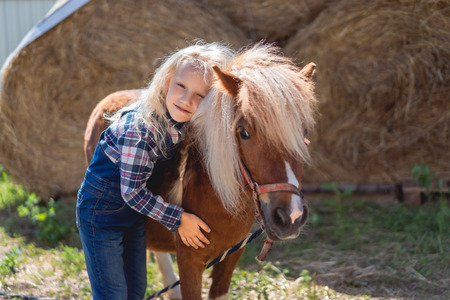 adorable kid touching hugging pony at ranch