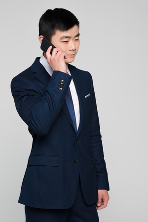 Half-length shot of concentrated businessman in a suit talking on the phone and looking away.