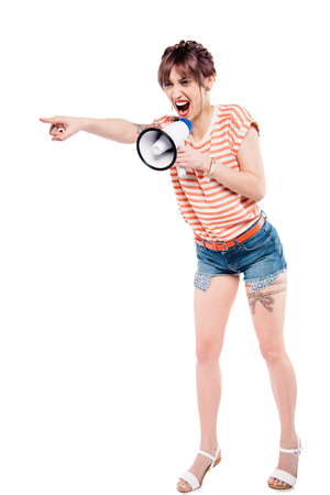 screaming young woman with loudspeaker pointing away isolated on white Imagens