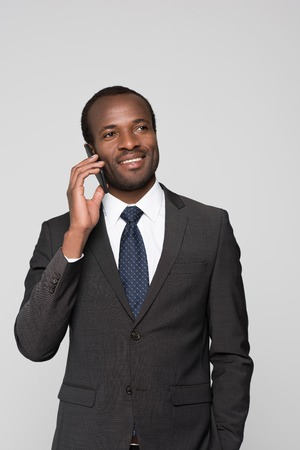 Half-length shot of smiling businessman in a suit talking on the phone.