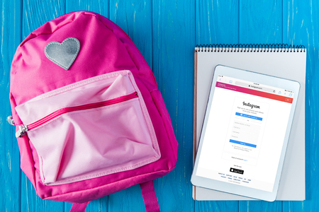 top view of pink backpack, blank textbook and digital tablet with instagram website on screen