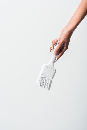 cropped image of girl holding painting brush with white paint isolated on white Standard-Bild - 105808457