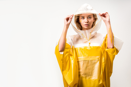 beautiful woman in raincoat holding hood and looking at camera isolated on white