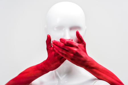 cropped image of woman in red paint covering mannequin mouth with hands isolated on white Stock Photo