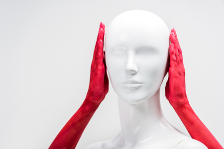cropped image of woman in red paint covering mannequin ears isolated on white Stock Photo