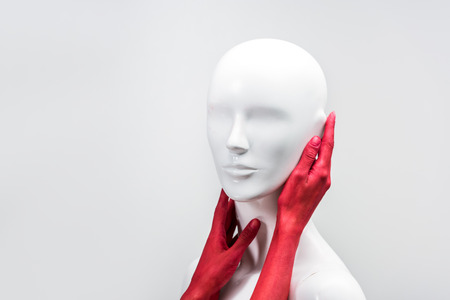 cropped image of woman in red paint touching mannequin neck and face isolated on white Banque d'images