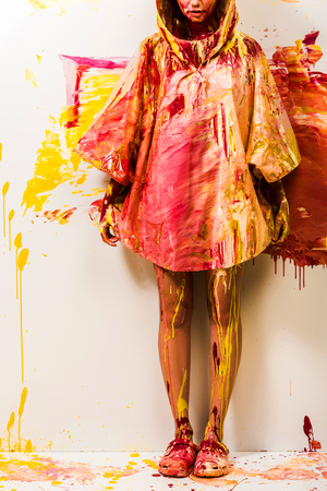 cropped image of woman standing in raincoat painted with yellow and red paints Stock fotó