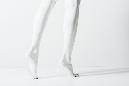 cropped image of girl with legs painted with white paint walking on white floor Foto de archivo - 105808832