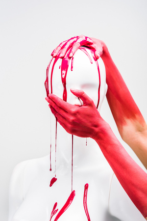 cropped image of woman in red paint covering mannequin mouth isolated on white