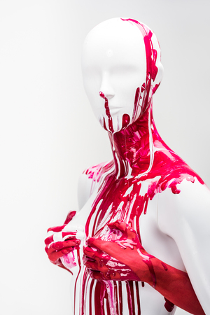 cropped image of girl in red paint touching mannequin breasts isolated on white Stock Photo