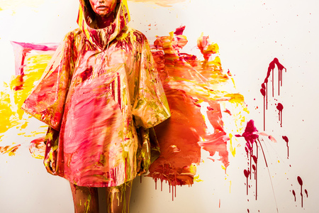 cropped image of woman standing in raincoat painted with yellow and red paints near wall Stock Photo