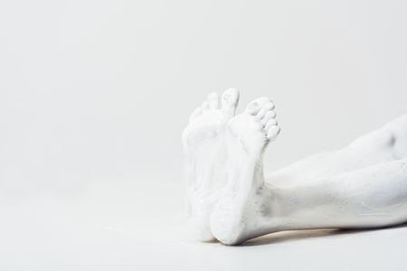 cropped image of woman with legs painted with white paint lying on floor on white Foto de archivo - 105809263
