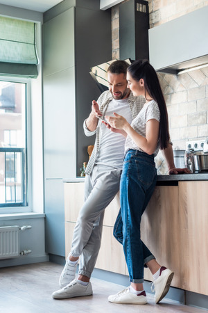 couple using smartphone together in kitchen, smart home concept Zdjęcie Seryjne