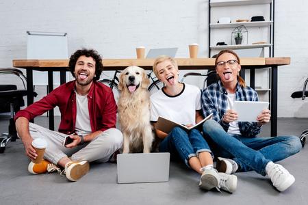 Heureux jeunes collègues et chien assis sur le sol avec des langues au bureau Banque d'images