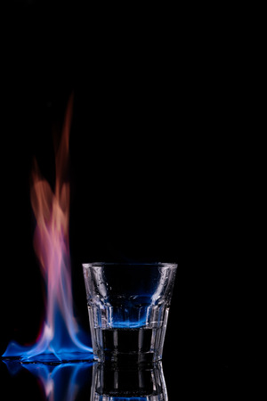 close up view of glass of burning sambuca drink on black background Stock Photo