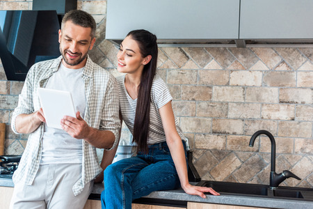 portrait of smiling couple using digital tablet together in kitchen, smart home concept
