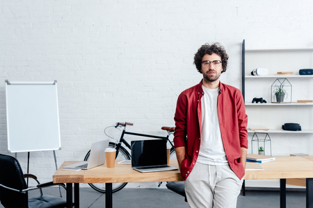 handsome young man in eyeglasses leaning at table and looking at camera in office