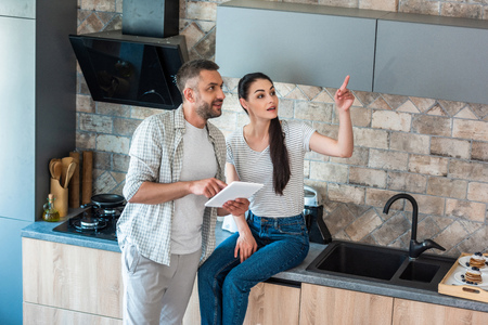married couple with digital tablet looking away in kitchen, smart home concept 写真素材