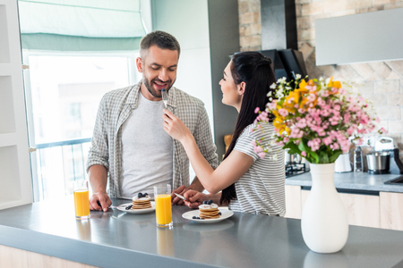 married couple having breakfast together in kitchen
