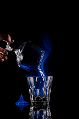 partial view of woman pouring burning sambuca alcohol drink into glass on black background