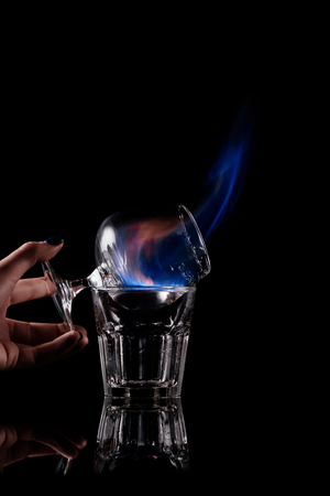 partial view of woman holding glass with burning sambuca alcohol drink on black background Stock Photo