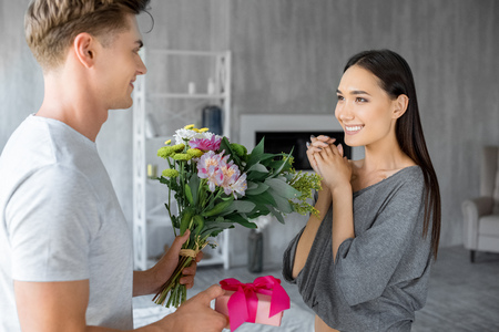 side view of caucasian man greeting smiling asian girlfriend with gift and bouquet of flowers at home