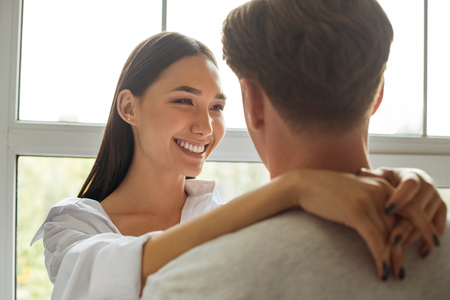 partial view of smiling asian woman hugging boyfriend at window