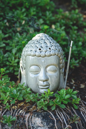 close up of Buddha head with aromatic smoking stick and plants around Imagens