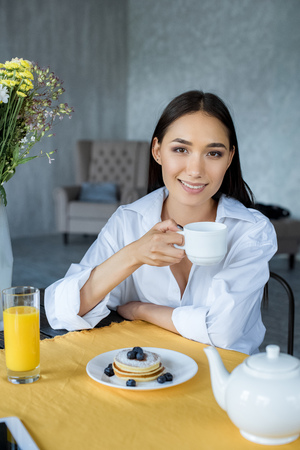 portrait of smiling asian woman with cup of tea at table with breakfast at home Banco de Imagens