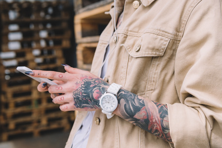 cropped image of tattooed woman with wristwatch using smartphone