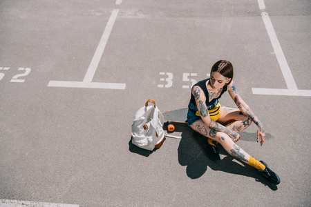 high angle view of stylish tattooed girl sitting on skateboard near backpack at parking lot