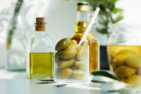 glass with spoon and green olives, jar, various bottles of aromatic olive oil with and branches on white table Stock Photo