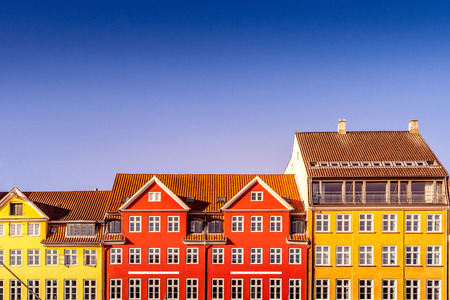 beautiful colorful historical houses against blue sky in copenhagen, denmark