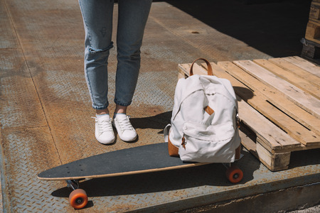 cropped image of woman standing near backpack and skateboard