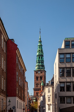 old tower with tall spire and historical buildings on street in copenhagen, denmark