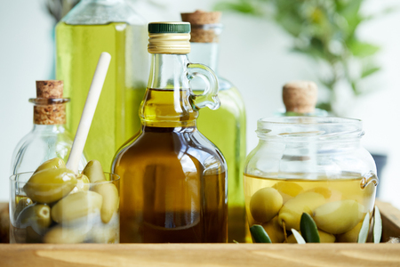 glass with spoon and green olives, jar, various bottles of aromatic olive oil with and branches on wooden tray Stock Photo