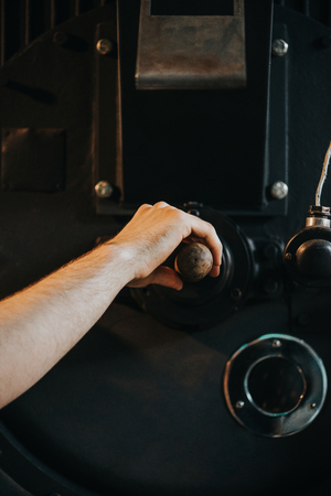 Male hand adjusting handle of machine for professional coffee production