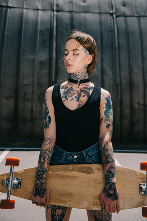 attractive stylish tattooed girl with closed eyes holding skateboard