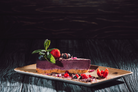 blueberry cake with strawberries, mint and viola petals on plate on wooden table Stock Photo