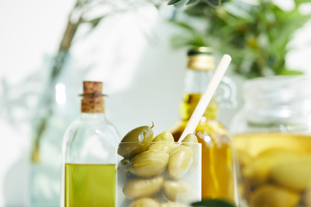 closeup shot of glass with spoon and green olives, jar, various bottles of aromatic olive oil with and branches on wooden tray 스톡 콘텐츠