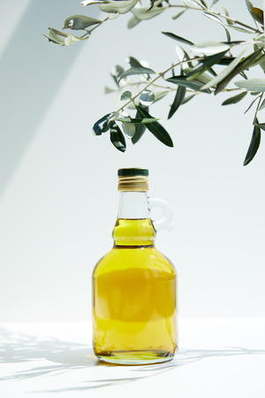 closeup view of bottle of aromatic olive oil and branches on white table 스톡 콘텐츠