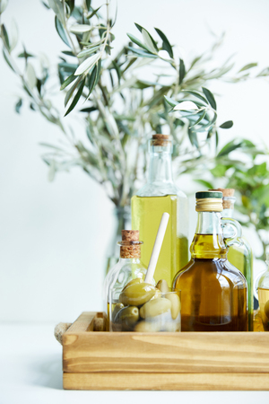 glass with spoon and green olives, various bottles of aromatic olive oil with and branches on wooden tray Stock Photo