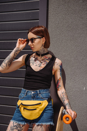 young stylish tattooed woman adjusting sunglasses and standing with skateboard Stock Photo
