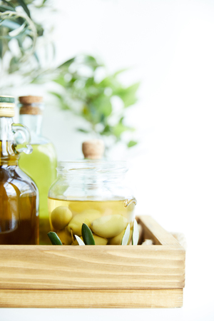 close up view of jar with green olives, bottles of aromatic olive oil with and branches on wooden tray Stock Photo