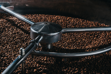 Aromatic coffee beans being roasted in professional machine Foto de archivo