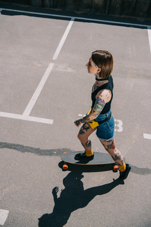 overhead view of stylish tattooed girl skateboarding at parking lot Stock Photo