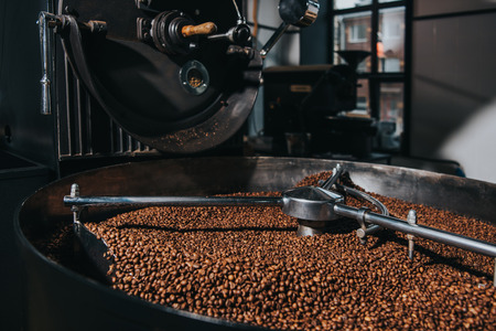 Interior of coffee production workshop with working coffee roasting machine Stok Fotoğraf